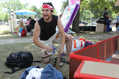 "Mike Greene - mgreene@shawmedia.com Tim Scordato, of Rockford, laughs while making a sword out of cardboard before the 28th Annual America's Cardboard Cup Regatta Saturday, June 23, 2012 at Main Beach in Crystal Lake. Scordato and a group of friends competed on the ""Gnihtemos""-- something spelled backwards."