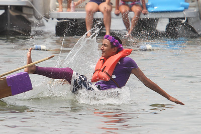 "Mike Greene - mgreene@shawmedia.com Juliano Gleichman, 16 of Crystal Lake, falls off his ship during the 28th Annual America's Cardboard Cup Regatta Saturday, June 23, 2012 at Main Beach in Crystal Lake. Gleichman and friends competed on the ""The paper mache didn't work, so now we're a bunch of grapes."""