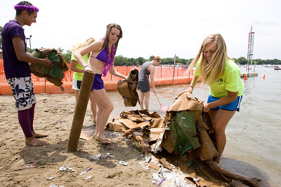 "Mike Greene - mgreene@shawmedia.com Members of ""The paper mache didn't work, so now we're a bunch of grapes"" and others pull the wreckage of the ship out of the water during the 28th Annual America's Cardboard Cup Regatta Saturday, June 23, 2012 at Main Beach in Crystal Lake."