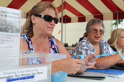 """Mike Greene - mgreene@shawmedia.com Volunteer Lisa Lang, of Woodstock, hands out raffle tickets during the 5th annual """"Remember Our Heroes"""" Car Show sponsored by VFW Post 5040 Saturday, June 23, 2012 in Woodstock. The annual event featured raffles from the post including a M1 Garand rifle and M1911 pistol as well as raffles from the Ladies' Auxiliary that included skin care products and homemade afghans. Proceeds from the event benefit VA Hospitals."""