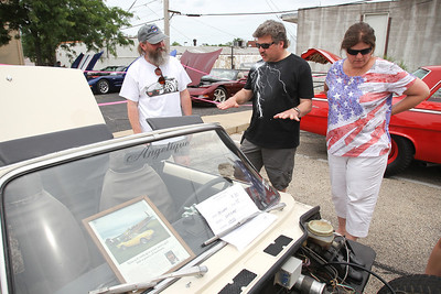 """Mike Greene - mgreene@shawmedia.com Scott Sanderson (center) and his wife Jenny, of Madison, WI, speak with Rick Schwede, of Salem, WI, during the 5th annual """"Remember Our Heroes"""" Car Show sponsored by VFW Post 5040 Saturday, June 23, 2012 in Woodstock. The annual event featured raffles from the post including a M1 Garand rifle and M1911 pistol as well as raffles from the Ladies' Auxiliary that included skin care products and homemade afghans. Proceeds from the event benefit VA Hospitals."""