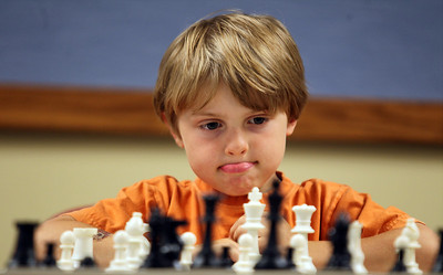 Sarah Nader - snader@shawmedia.com Jack Kerth, 6, of McHenry pounders his next move while playing chess champion Bob Cairone of Crystal Lake during a chess tournament hosted by the Crystal Lake Public Library on Tuesday, June 26, 2012.