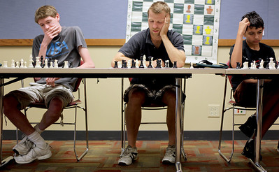 Sarah Nader - snader@shawmedia.com Dan Rosenthal (left), 16, of Fox River Grove, Dave Kerth of McHenry and Brandon Harisis, 13, of Crystal Lake pounder their next move during a chess tournament hosted by the Crystal Lake Public Library on Tuesday, June 26, 2012.