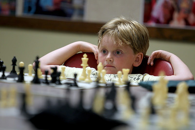 Sarah Nader - snader@shawmedia.com Paul Sweeney, 8, of Algonquin waits for his next turn while playing chess champion Bob Cairone of Crystal Lake during a chess tournament hosted by the Crystal Lake Public Library on Tuesday, June 26, 2012.