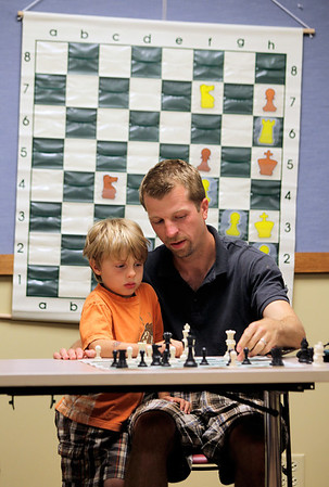Sarah Nader - snader@shawmedia.com Jack Kerth, 6, of McHenry helps his dad, Dave, make his next move while playing chess champion Bob Cairone of Crystal Lake during a chess tournament hosted by the Crystal Lake Public Library on Tuesday, June 26, 2012.