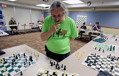Sarah Nader - snader@shawmedia.com Bob Cairone of Crystal Lake pounders his next move while playing 17 consecutive games of chess during a tournament hosted by the Crystal Lake Public Library on Tuesday, June 26, 2012. The Crystal Lake Library hosted seven weeks of chess workshops to help learn strategy, positioning and logic before hosting the tournament against Cairone.