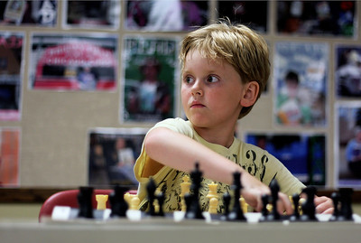 Sarah Nader - snader@shawmedia.com Paul Sweeney, 8, of Algonquin makes a move while playing against chess champion Bob Cairone of Crystal Lake during a chess tournament hosted by the Crystal Lake Public Library on Tuesday, June 26, 2012.