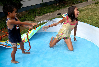 Josh Peckler - Jpeckler@shawmedia.com Yosgard Salazar, 3 of Crystal Lake sprays his sister Lesly, 8 with water as they play in a small pool outside their home in Crystal Lake Thursday, June 28, 2012. With temperatures reaching near 100 degrees on Thursday, many people found their own ways to stay cool in the heat.