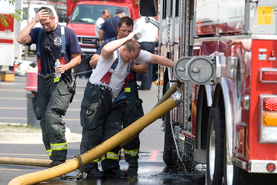 Mike Greene - mgreene@shawmedia.com Firefighters cool off using a East Dundee Fire Department truck while fighting a fire at Community Thrift Store Thursday, June 28, 2012 in East Dundee. Local and regional fire crews teamed up to take turns dealing with the fire in the scorching heat.