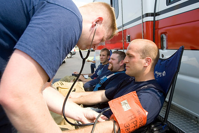 Mike Greene - mgreene@shawmedia.com Dan Nicholson, of the Hanover Park fire department, checks Carpentersville firefighter Matt Jackson's blood pressure while at a fire at Community Thrift Store Thursday, June 28, 2012 in East Dundee. Local and regional fire crews teamed up to take turns dealing with the fire in the scorching heat.