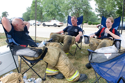 Mike Greene - mgreene@shawmedia.com Carpentersville firefighters Hector Gonzalez (left), Erik Vogel, and Monika Stawski cool off in chairs with ice bags while fighting a fire at Community Thrift Store Thursday, June 28, 2012 in East Dundee. Local and regional fire crews teamed up to take turns dealing with the fire in the scorching heat.