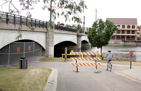 Tye Barrett, who is visiting the area from Waco, Texas, rides his bicycle past barricades marking the closure of the Fox River Trail connection to Island Park in Geneva.