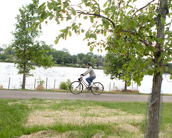 A biker passes through Bennett Park on the Fox River Trail in St. Charles Friday.