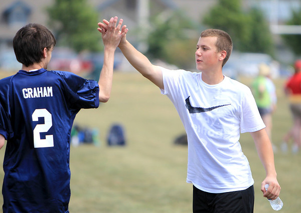 "Former Tri City Chargers player Michael Hurst gives a high-five to Grahaml, a student at Giant Steps in Lisle, during a one-day camp at James O. Breen Park in St. Charles Thursday morning. The camp pairs a current or former Tri City Charger player with a ""buddy"" from Giant Steps, which is a school for students with autism spectrum disorder."