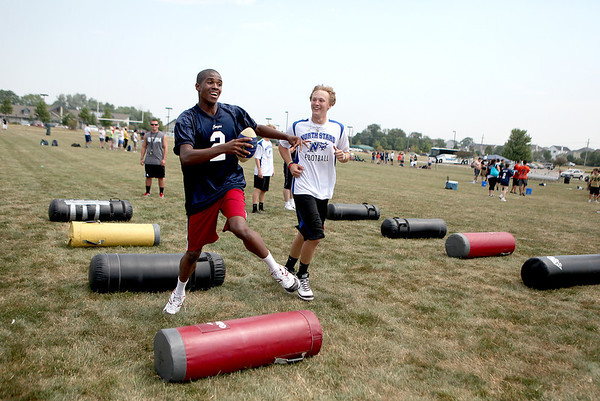 "Former Tri City Chargers player Kevin Dawrant (right) tries to keep up with Daniel, a student at Giant Steps in Lisle, during a one-day camp at James O. Breen Park in St. Charles Thursday morning. The camp pairs a current or former Tri City Charger player with a ""buddy"" from Giant Steps, which is a school for students with autism spectrum disorder."