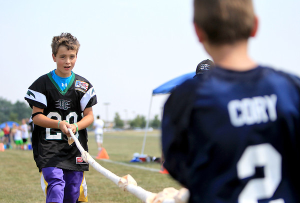 """Tri City Chargers player Conor Dixon, 12, plays tug-o-war with Coryl, a student at Giant Steps in Lisle, during a one-day camp at James O. Breen Park in St. Charles Thursday morning. The camp pairs a current or former Tri City Charger player with a """"buddy"""" from Giant Steps, which is a school for students with autism spectrum disorder."""