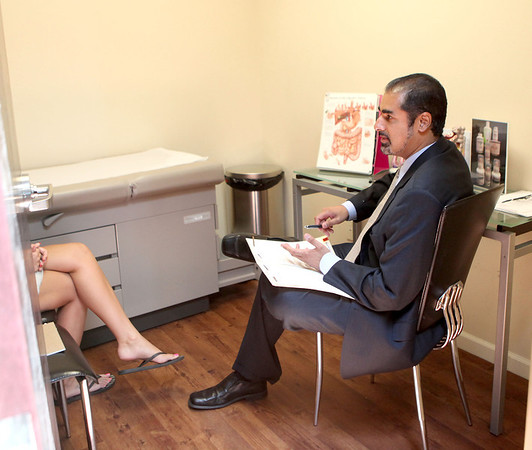 Dr. Tarun Mullick meets with patient Sarah Tighe in his Geneva office Thursday.