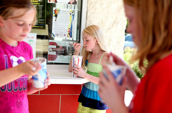 (Right to left) Lauren Haefer, 9, Camille Drancik, 8, and Mara Drancik, 10, enjoy a cool treat on a hot day Monday afternoon at Moolala in Batavia.