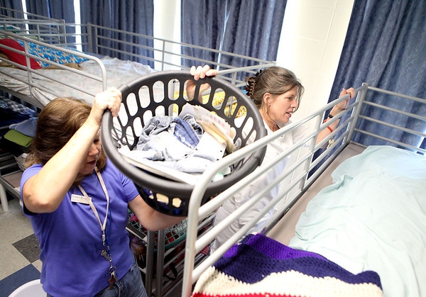 Lazarus House staff members Wanda Hochstetter (left) and Carol Migacz clean one of the St. Charles facility's  bed areas Tuesday afternoon. Lazarus House is celebrating 15 years of service to the community this year.