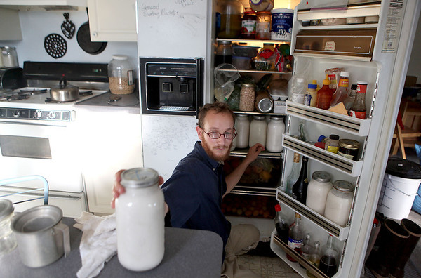 Elan Margulies stocks his refrigerator with fresh goat's milk at his organic farm in Geneva early Wednesday morning. Margulies is in his second season running Pushing the Envelop Farm.