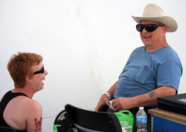 Maureen Ruski, of Decatur, talks with Jerry Sentowski, of Chicago, after giving him an air brush tattoo Sunday during River Fest in St. Charles.