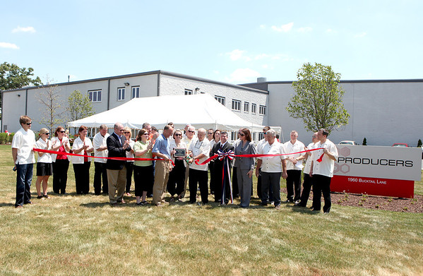 Sugar Grove Village President Sean Michels (front row, third from left) helps Producers Chemical Company owner Roger Harris (fifth from left) and his wife, Jane, cut the ribbon to officially open the company's new Sugar Grove location at 1960 Bucktail Lane. The decades-old company was previously located in Batavia