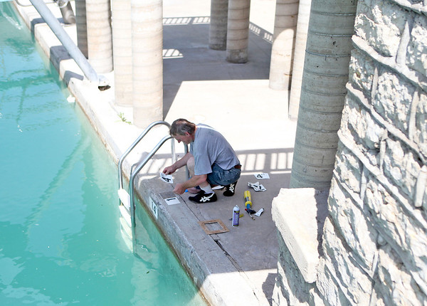 Batavia Park District employee Doug Martens applies new depth markers at Harold Hall Quarry Beach in Batavia. The depth of the water changed from 17 feet to 14 feet because of a new liner installed.