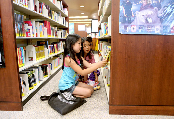 Karmyn Hookham (left) and Yuki Tanizaki, both 8, look for books during a kick-off of the Elburn Town and Country Public Library's summer reading program Monday night.