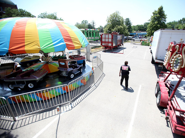 Lonnie Piper, an employee of Windy City Amusements, walks through the carnival area during set-up in preparation for the 2012 Swedish Days Festival in downtown Geneva. The festival runs today through Sunday.