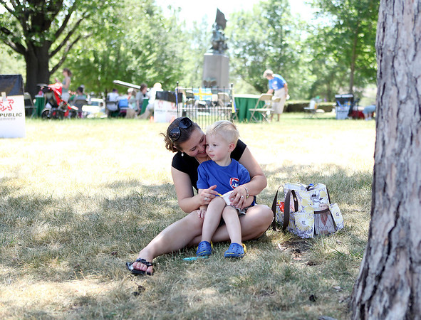 Sanja Harvey and her son, Noah, 3, find some shade on the lawn of the Kane County Courthouse during Swedish Days Wednesday.