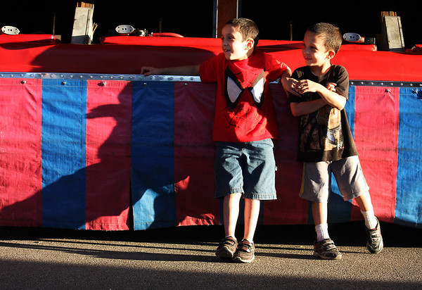 Josh, Left, and Matthew, right, Woods, of Chicago, stand by a carnival game during Swedish Days Thursday in Geneva.