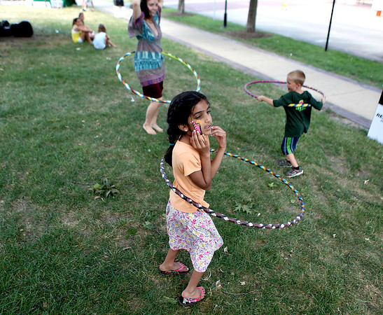 Seven-year-old Karishma Patel twirls a hoop with Hayley Caddy and Preston Popovich, 5, on the lawn of the Kane County Courthouse during the opening day of Swedish Days in downtown Geneva Tuesday.