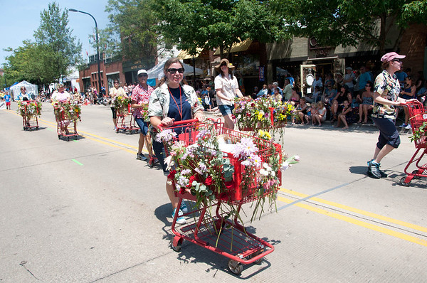 Trader Joe's employees push carts full of natural flowers as part of the Swedish Days Parade in Geneva Sunday afternoon.