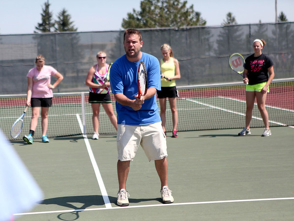Kaneland High School teacher and tennis coach Tim Larsen works with participants of a summer tennis camp at the school Monday morning.