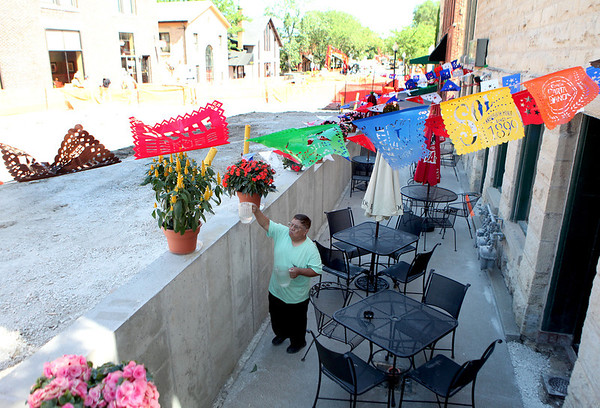 Manuel Martinez waters flowers at El Taco Grande along River Street in downtown Batavia. River Street is currently closed to traffic due to construction.