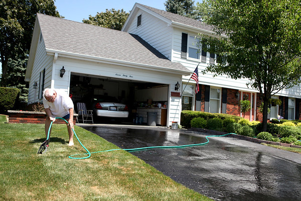 Ralph Hartwig adjusts the sprinkler outside his St. Charles home.
