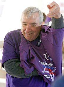 Peter Wuertz, Indian Head Park puts on his survivor t-shirt before heading out to the track. The annual Relay For Life for the Barrington area brings survivors, care-takers and volutneers to the athletic track at Barrington High School to celebrate life, honor the memory of those gone and help raise funds for research and a cure.. | Joe Cyganowski-For Barrington Life