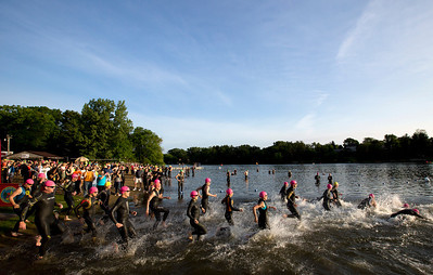 Competitors run into the water to start the first leg of the Lake in the Hills Triathlon on Sunday. Brett Moist / For the Northwest Herald