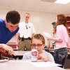 James Sargent, 13, (left) and Grant Landbo, 13, (center) both of St. Charles, investigate a piece of evidence as Officer Bill Tynan (background) watches during the St. Charles Police Department Youth Academy mock crime scene at St. Charles North High School Tuesday. The mock crime scene was staged as a burglary at St. Charles North High School by the St. Charles Police Department.