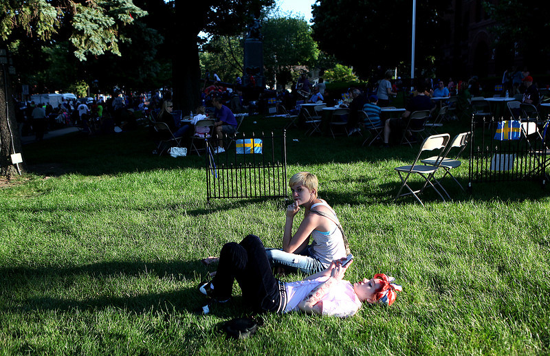 Amy Premo (laying down) and Beth Mehl, both of St. Charles, wait for the band 7th Heaven to begin during the Swedish Days Festival Tuesday evening in Geneva.