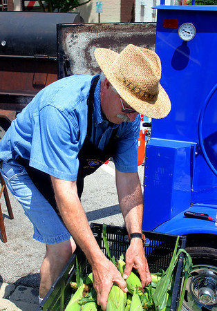 Nick Hall, the Grand Master of the local Knights of Columbus branch, and a resident of Batavia, loads corn into a Texas-made corn roaster at the Knights of Columbus food tent during Geneva's annual Swedish Days festival on Wednesday. The Knights of Columbus branch covers Elburn, Geneva, and Batavia, so members from all three towns came out to assist.