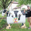 "Mike McCormick stands in front of his house in Batavia next to ""Melba the Route 25 Cow.""  McCormick and his wife Kelly have worked on the cow for a year and a half, decorating it for major holidays such as Christmas and Memorial Day. McCormick is working on a Blackhawks themed outfit for Melba to celebrate the Blackhawks' berth in the Stanley Cup Finals."