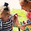 Emilie Patterson, 2, of Geneva gets her face painted by Marisa Lewis during the Swedish Days Festival in Geneva Tuesday.