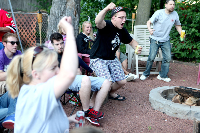Anthony Humbles (center) leaps out of his seat as the Chicago Blackhawks score a goal in the first period of Wednesday's game against the Boston Bruins. Humbles and many others were watching the game in the backyard of St. Charles resident Tom Campana, who projects the game onto a large screen that hangs from his porch.