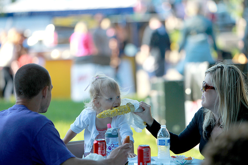Sheryl Dugena feeds her daughter, Claire, 2, an ear of corn as Claire's dad, Justin Dugena, looks on during  Swedish Days Festival Tuesday evening in Geneva.