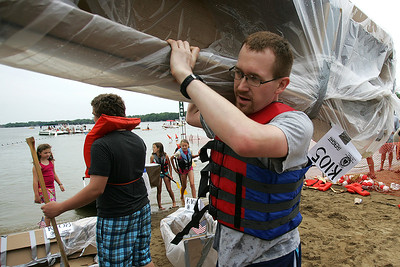Kyle Grillot - kgrillot@shawmedia.com   Wes Brazas of Hampshire carries his boat onto land after competing in the 29th annual America's Cardboard Cup Regatta at the Crystal Lake Park District's Main Beach June 22, 2013. The competition raises money for local charities, contributing more than $500,000 since the first event. Entry fees are $20 per family and $200 per business with a $3 general admission fee per person that is capped at $15 per family. The event draws more than 2,000 people per year.
