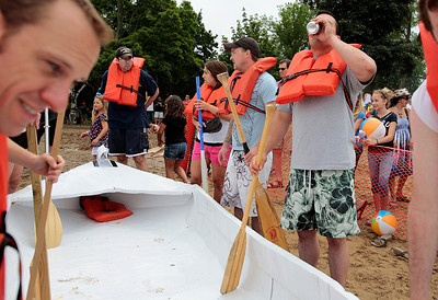 Kyle Grillot - kgrillot@shawmedia.com   Participants prepare to place a boat in the water before the start of a race during the 29th annual America's Cardboard Cup Regatta at the Crystal Lake Park District's Main Beach June 22, 2013. The competition raises money for local charities, contributing more than $500,000 since the first event. Entry fees are $20 per family and $200 per business with a $3 general admission fee per person that is capped at $15 per family. The event draws more than 2,000 people per year.