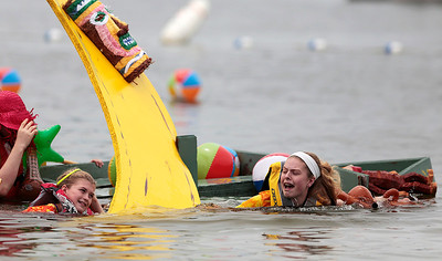"Kyle Grillot - kgrillot@shawmedia.com   Kate Smeenge, 11, (left) and Kelsey Smith, 11, both of Crystal Lake pull their boat ""Go Bananas"" to shore after capsizing during the 29th annual America's Cardboard Cup Regatta at the Crystal Lake Park District's Main Beach June 22, 2013. The competition raises money for local charities, contributing more than $500,000 since the first event. Entry fees are $20 per family and $200 per business with a $3 general admission fee per person that is capped at $15 per family. The event draws more than 2,000 people per year."