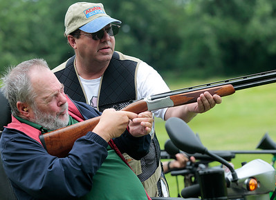 Kyle Grillot - kgrillot@shawmedia.com   Veteran Keith Wetzstein of Woddstock (left) is helped by Jay Adams of McHenry while firing a shotgun during the first annual Joe's Wish shootout for paralyzed veterans Saturday at the McHenry Sportsman's Club. Joe's Wish, a nonprofit that helps area veterans hosted the event and McHenry Sportsman's Club donated their facilities, staff, and clays.