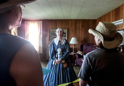 Sarah Nader - snader@shawmedia.com Volunteer reenactor Marie Wilt of McHenry shows people around the farm house during the annual Day at Petersen Farm in McHenry Sunday, June 23, 2013. The theme of this years event honored McHenry County's historic dairy industry. The event featured traditional hayrides, children's games, crafts demonstrations, farm equipment displays and a farm garden.